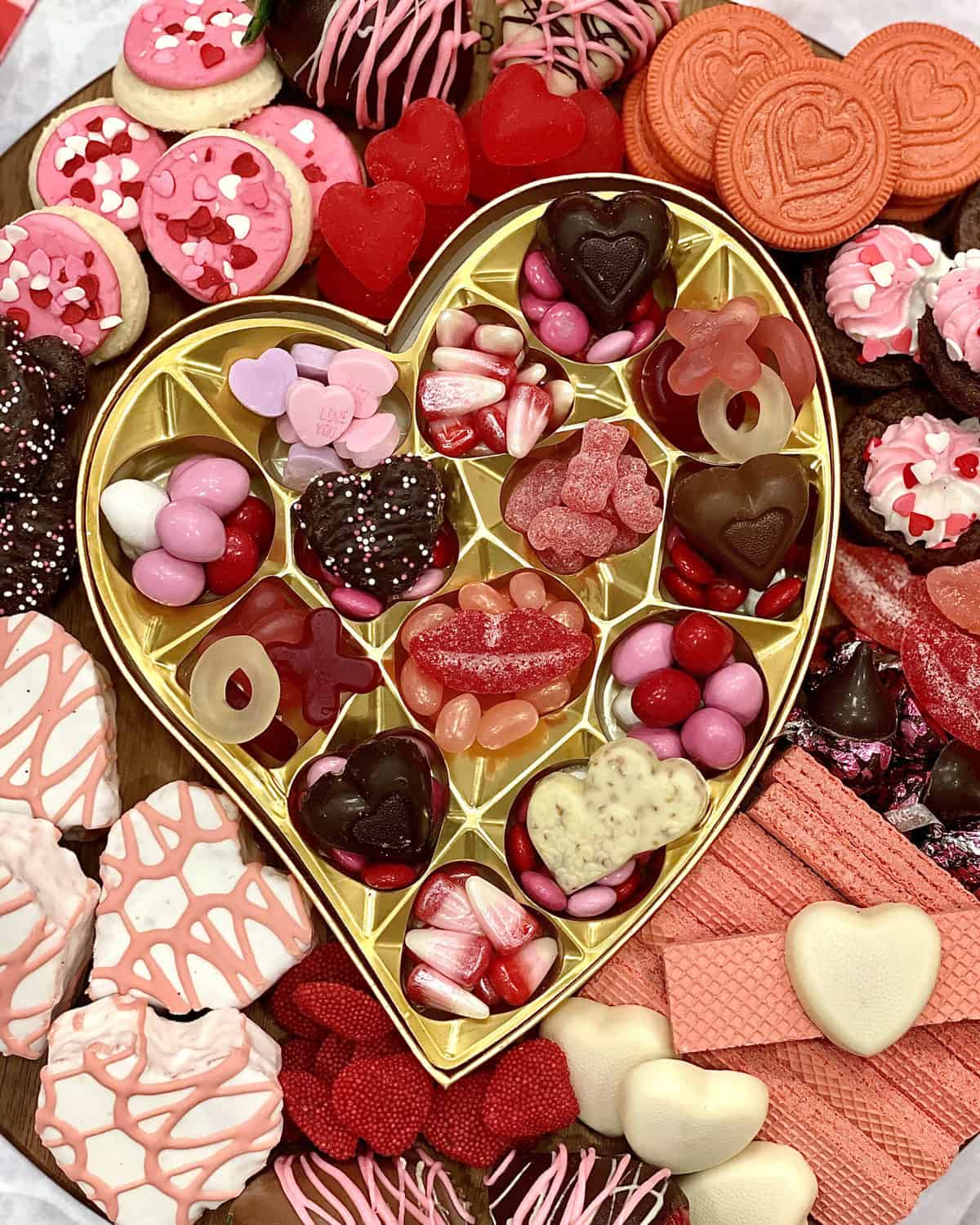 Dessert Board with heart-shaped cakes, conversation hearts, M&Ms, pink and white sugar cookies