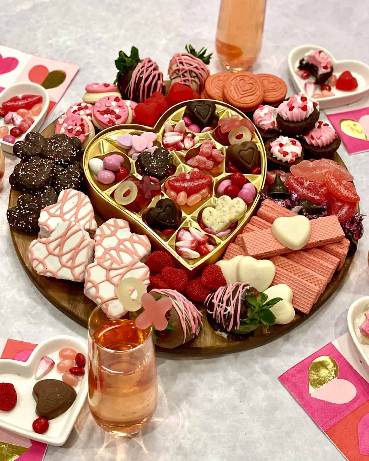 Galentine's Day Dessert Board with heart-shaped cakes, conversation hearts, M&Ms, pink and white sugar cookies
