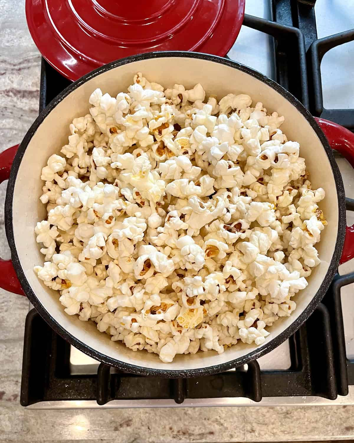 Stovetop Popcorn in a red pot on the stove.